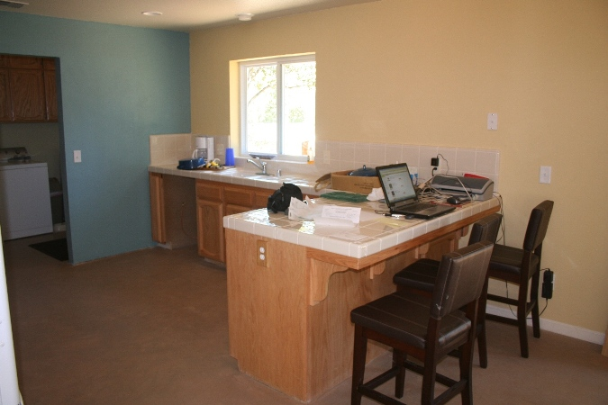 The living room wall extends into the kitchen. Funny to see now our little home office set up on the kitchen counter.